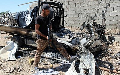 A member of Iraqi government forces inspects a burnt vehicle with a flag of the Islamic State (IS) on its top after they retook an area from jihadists on April 2, 2016 in the village of Al-Mamoura, near Hit, a Euphrates Valley town located about 145 kilometers west of Baghdad in the western province of Anbar. (Moadh al-Dulaimi/AFP)