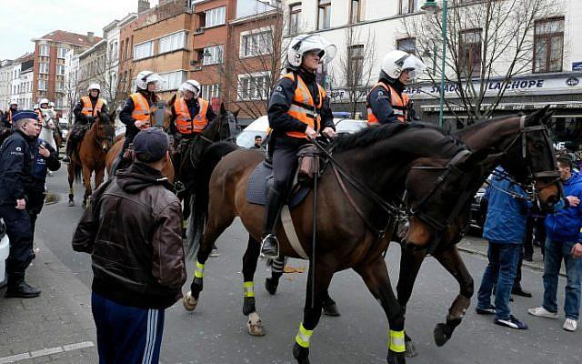 Local youth and police on horseback gather in the street of Molenbeek-Saint-Jean in Brussels, on April 2, 2016. (Nicolas Maeterlinck/Belga/AFP)