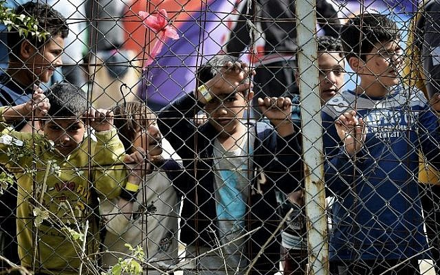 Children stand behind a fence inside the Moria migrant camp transformed in police-run detention facility in Mytilene, on Lesbos island on April 3, 2016. (AFP / ARIS MESSINIS)