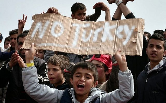 """Refugees and migrants including children who left the Chios registration camp, shout slogans and hold placards reading """"'No Turkey"""" during a protest on April 3, 2016 as they camp out in the port of Chios. (AFP / LOUISA GOULIAMAKI)"""