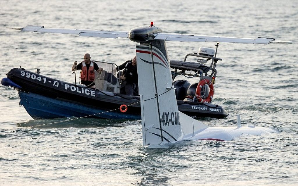 A rescue boat works to secure a cable around the tail of a light aircraft after it made an emergency landing in the Mediterranean Sea off the shore of Tel Aviv, on April 3, 2016.  (AFP/JACK GUEZ)