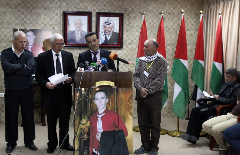 Palestinian doctor, Rayan al-Ali, who carried out the autopsy on 21-year-old Palestinian Abdul Fatah al-Sharif, pictured on poster, speaks during a press conference in the West Bank town of Hebron on April 4, 2016. (AFP / HAZEM BADER)