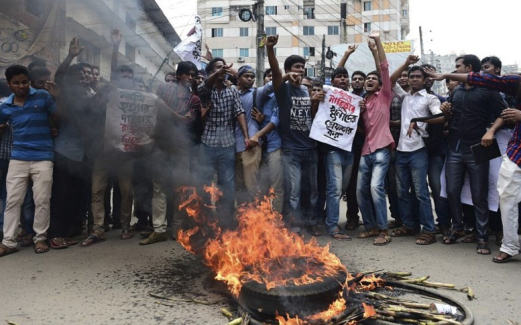 Bangladeshi students block the road and stage a protest following the murder of a law student, hacked to death by four assailants the night before, in Dhaka on April 7, 2016. (AFP PHOTO / Munir UZ ZAMAN)