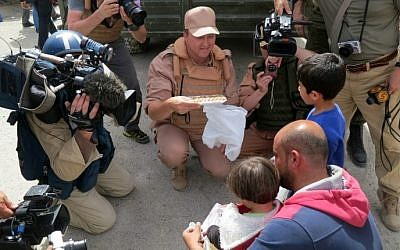 A picture taken during a press tour organized by the Russian Army shows Russian journalists working next to a Russian soldier talking with Syrians on April 8, 2016 in al-Qaryatain. (AFP PHOTO / Max DELANY)