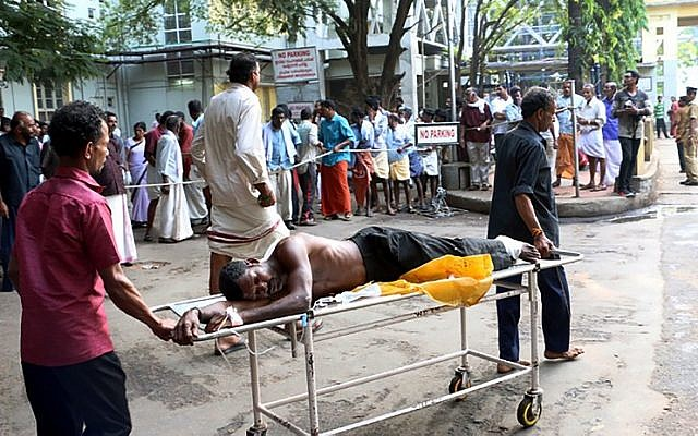 Indian medical officials and bystanders use a trolley to transport an injured man from a vehicle into a hospital in Paravur on April 10, 2016, after an explosion and fire at The Puttingal Devi Temple in the southern Indian state of Kerala. (AFP PHOTO / STR)