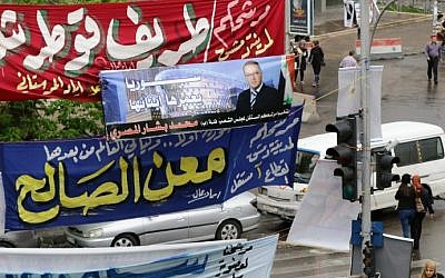 Syrians walk past campaign banners of candidates for the upcoming parliamentary elections in Damascus on April 12, 2016. (AFP PHOTO / LOUAI BESHARA)