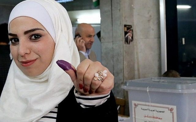 A Syrian woman shows her ink stained thumb after voting at a polling station during parliamentary elections in Damascus on April 13, 2016. (AFP Photo/Joseph Eid)