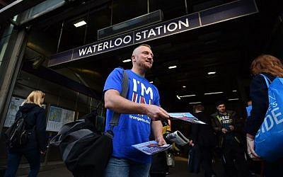 A campaigner with Britain Stronger in Europe, the official Remain campaign in June's EU referendum, hands out leaflets to commuters outside Waterloo Station in London on April 14, 2016. (AFP PHOTO/BEN STANSALL)