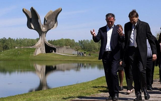 Illustrative: Members of the Jewish community walk in front of a memorial in the shape of a flower in Jasenovac on April 15. 2016. (AFP PHOTO / STRINGER)