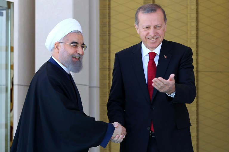 Turkish President Recep Tayyip Erdogan shakes hands with his Iranian counterpart Hassan Rouhani during an official welcoming ceremony at the presidential complex in Ankara on April 16, 2016. (AFP PHOTO / ADEM ALTAN)