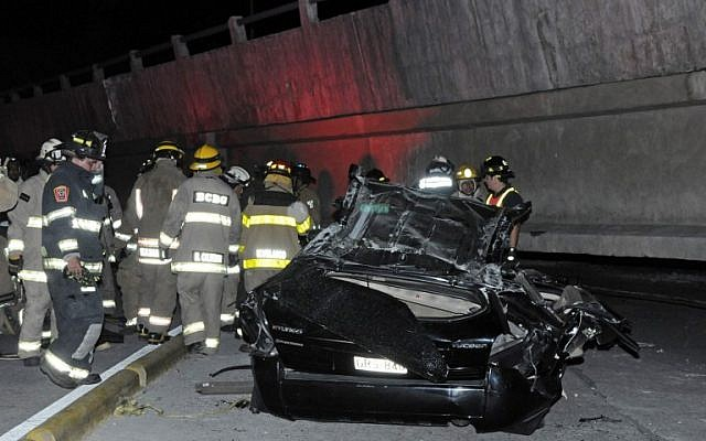 Rescue workers stand before a destroyed car after the collapse of a bridge in an earthquake, in Guayaquil, Ecuador, April 16, 2016. (AFP/MARCOS PIN MENDEZ)