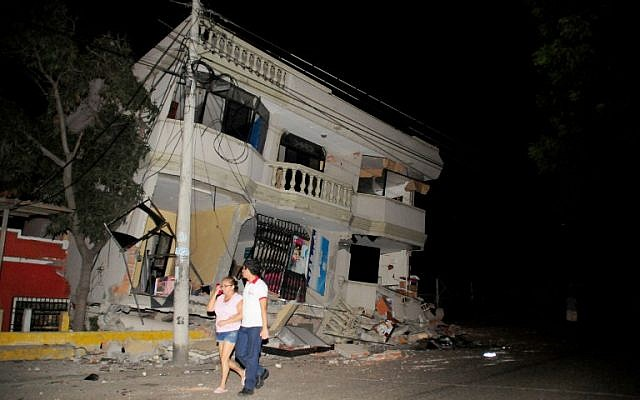 Residents walk on a street amid destroyed buildings following an earthquake, April 16, 2016 in Guayaquil, Ecuador. (AFP PHOTO / ARIEL OCHOA)