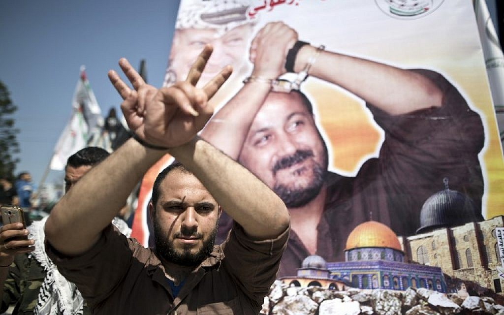 A Palestinian man gestures in front of a poster bearing the portrait of jailed Fatah leader Marwan Barghouti, during a rally marking Palestinian Prisoner Day in Gaza City on April 17, 2016. (AFP PHOTO/MAHMUD HAMS)