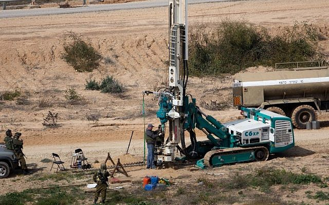 This February 10, 2016, file photo shows IDF soldiers keeping watch as a machine drills holes in the ground on the Israeli side of the border with the Gaza Strip as they search for tunnels used by Palestinian terrorists planning to attack Israel. (AFP/Menahem Kahana)