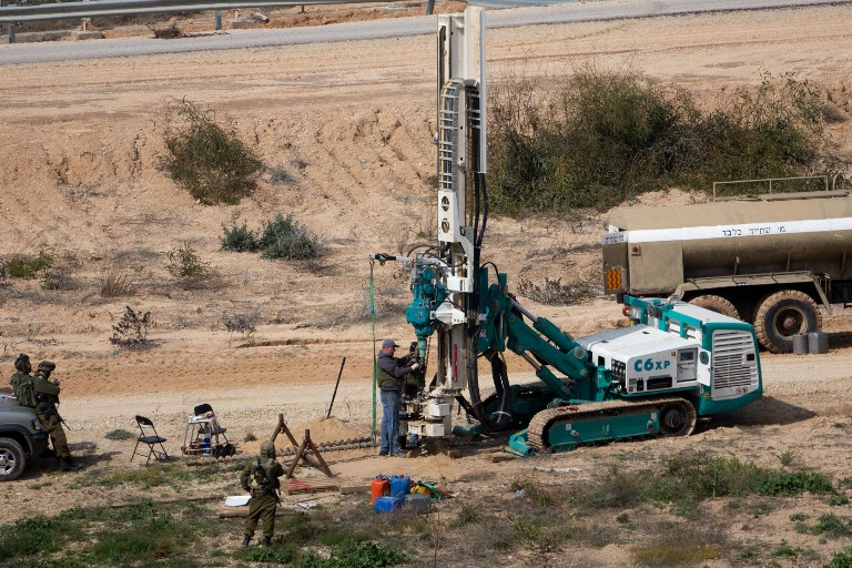 This February 10, 2016 file photo shows IDF soldiers keeping watch as a machine drills holes in the ground on the Israeli side of the border with the Gaza Strip as they search for tunnels used by Palestinian terrorists planning to attack Israel. (AFP PHOTO/MENAHEM KAHANA)