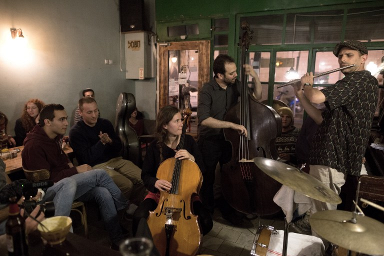 Foreign musicians (R) and (L) play with the Ehud Ettun trio during a Jazz concert at the Hamarakia soup restaurant in centre of Jerusalem on April 12, 2016. (AFP PHOTO / MENAHEM KAHANA)