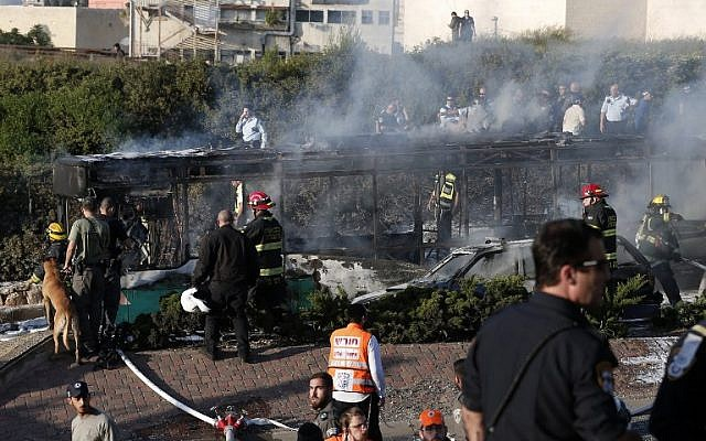 Israeli security forces and emergency services gather around a burnt-out bus following an explosion in Jerusalem on April 18, 2016. (AFP PHOTO / THOMAS COEX)