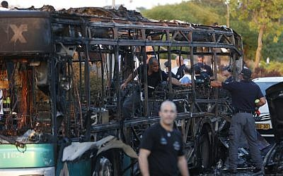 Israeli police check a burned-out bus that was blown up in a terror attack in Jerusalem on April 18, 2016. (AFP/Ahmad Gharabli)