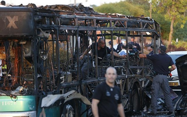 Israeli police check a burnt-out bus following an explosion in Jerusalem on April 18, 2016. (AFP PHOTO / AHMAD GHARABLI)
