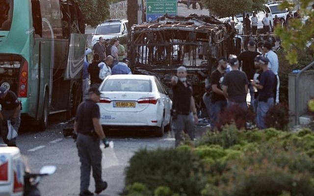 Israeli security forces and forensics technicians investigate the scene of a bus explosion in southern Jerusalem on April 18, 2016. (Thomas Coex/AFP)