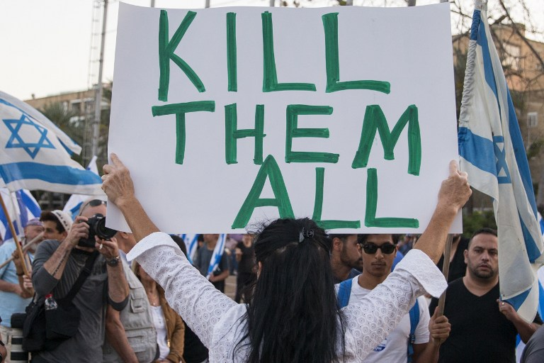 A woman holds up a sign with 'Too many terrorists in prison' written on one side and 'Kill them all' written on the other during a rally in Tel Aviv on April 19, 2016 to support Elor Azria, an Israeli soldier recently charged with manslaughter after shooting a prone and wounded Palestinian assailant in the head. (Jack Guez/AFP)