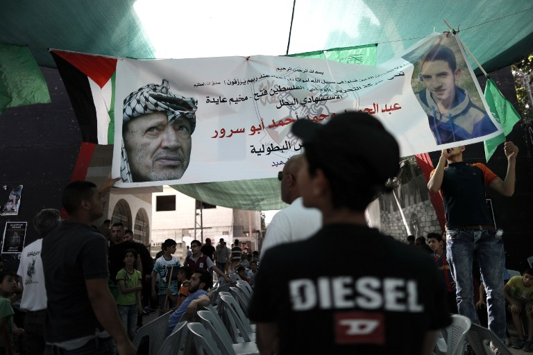 Palestinians gather under a banner depicting bus bomber Abdel Hamid Abu Sorur and Yasser Arafat, at al-Ayda refugee camp on April 21, 2016. (AFP PHOTO / THOMAS COEX)