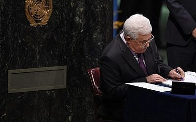 Palestinian Authority President Mahmud Abbas signs papers at the high level signature ceremony for the Paris Agreement at  the United Nations General Assembly Hall on April 22, 2016 . (AFP PHOTO/TIMOTHY A. CLARY)