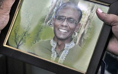 A man holds a portrait of Bangladeshi professor Rezaul Karim Siddique, who was hacked to death by unidentified attackers, in Rajshahi on April 23, 2016.  (Md. Abdullah Iqbal/AFP)