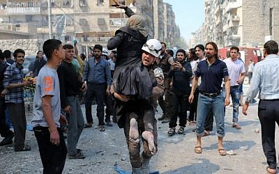A Syrian civil defense volunteer evacuates a woman following a reported airstrike on April 23, 2016 in the rebel-held neighborhood of Tareeq al-Bab in the northern city of Aleppo. (Ameer Alhalbi/AFP)