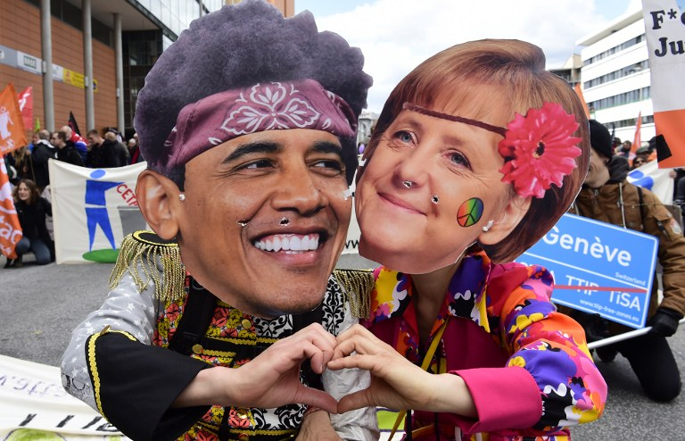 Protesters wearing masks featuring German Chancellor Angela Merkel and US President Barack Obama pose during a prostest rally on the eve of US President's vist to Hannover on April 23, 2016 (AFP PHOTO / John Macdougall)