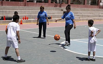 Palestinian physical education teachers (blue) and schoolchildren take part in a training session organized by the Real Madrid Foundation at a UN run school in the Qalandia refugee camp in the West Bank, April 25, 2016. (AFP/ABBAS MOMANI)
