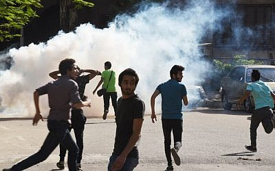 Egyptian protesters run for cover from tear gas fired by riot police during a Cairo demonstration against the handing over of two Red Sea islands to Saudi Arabia, April 25, 2016. (AFP Photo/Mohamed el-Shahed)
