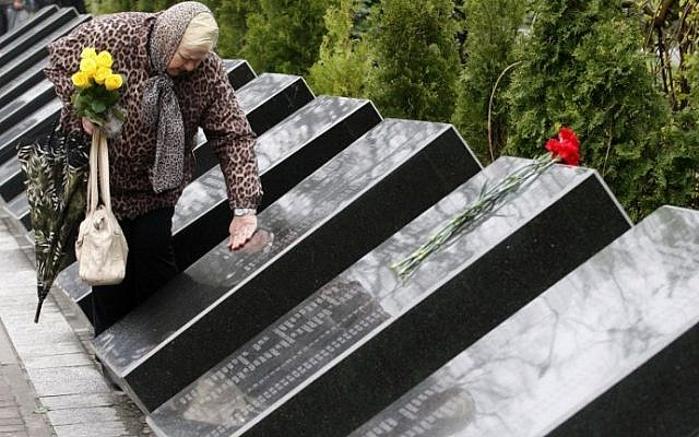 A woman mourns at the Chernobyl victims' memorial in the Ukrainian capital of Kiev on April 26, 2016. (AFP PHOTO / Anatolii Stepanov)