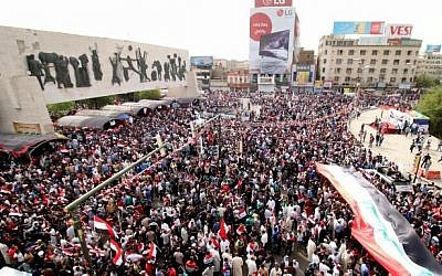 Iraqi supporters of the Sadrist movement hold national flags and shout slogans during a demonstration to press for reforms on April 26, 2016, at Baghdad's Tahrir Square. (AFP PHOTO / HAIDAR MOHAMMED ALI)
