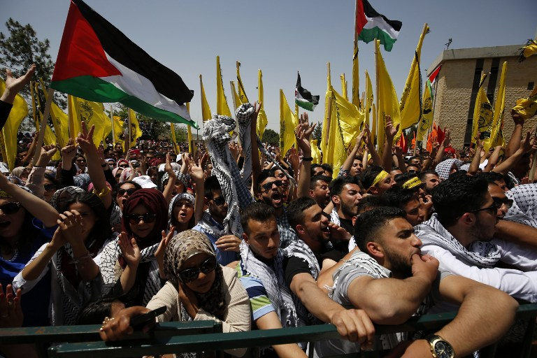 Palestinian students supporting the Fatah movement wave both the national and the movement's flag during an election campaign rally for the student council at the Birzeit University, near the West Bank city of Ramallah on April 26, 2016 (AFP PHOTO / ABBAS MOMANI)