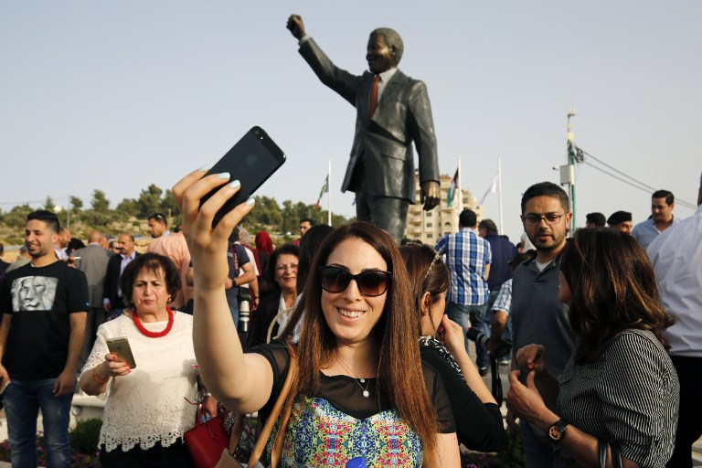 A Palestinian woman takes a selfie in front of a giant statue of Nelson Mandela following its inauguration ceremony in the West Bank city of Ramallah on April 26, 2016. Palestinians inaugurated the statue of Mandela donated by the South African city of Johannesburg to their political capital. The six-metre (20-foot) two-tonne bronze statue was a gift from Johannesburg with which Ramallah is twinned. / AFP PHOTO / ABBAS MOMANI