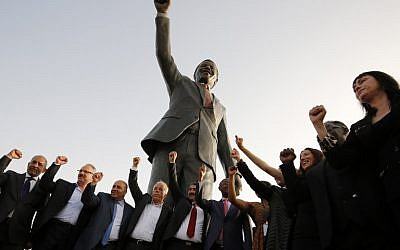 Palestinian and South African officials pose in front of a giant statue of Nelson Mandela during its inauguration ceremony in the West Bank city of Ramallah on April 26, 2016. (AFP PHOTO / ABBAS MOMANI)