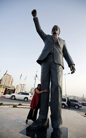 A woman poses in front of a giant statue of Nelson Mandela following its inauguration ceremony in the West Bank city of Ramallah on April 26, 2016. (AFP PHOTO / ABBAS MOMANI)