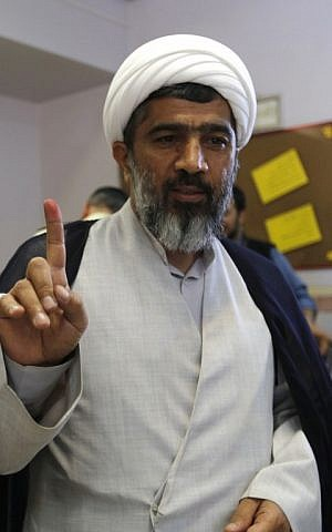An Iranian cleric displays his ink-stained finger after casting his ballot for the second round of parliamentary elections at a polling station in the town of Robat Karim, some 40 kms southwest of the capital Tehran, on April 29, 2016. (AFP PHOTO/ATTA KENARE)