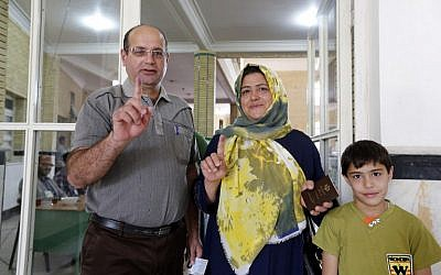 Iranian family members display their ink-stained fingers after casting their ballot to vote in the second round of parliamentary elections at a polling station in the town of Robat Karim, some 40 kms southwest of the capital Tehran, on April 29, 2016. (AFP/Atta Kenare)