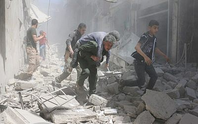 Syrians evacuate an injured man amid the rubble of destroyed buildings following a reported air strike on the rebel-held neighborhood of Al-Qatarji, in the northern Syrian city of Aleppo, on April 29, 2016. (AFP/Ameer Alhalbi)