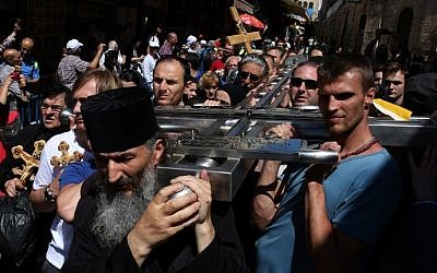 Serbian Orthodox Christian pilgrims carry a large metal cross from Serbia along the Via Dolorosa (Way of Suffering), during the Good Friday procession in Jerusalem's Old City on April 29, 2016. (Gali Tibbon/AFP)
