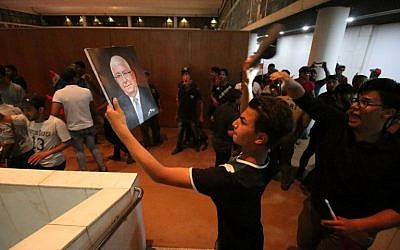 """An Iraqi protester uses a shoe to hit a portrait of President Fuad Masum inside the parliament after breaking into Baghdad's heavily fortified """"Green Zone"""" on April 30, 2016.  Thousands of angry protesters broke into Baghdad's Green Zone and stormed the parliament building after lawmakers again failed to approve new ministers. Jubilant supporters of cleric Moqtada al-Sadr invaded the main session hall, shouting slogans glorifying their leader and claiming that they had rooted out corruption. (AFP PHOTO / HAIDAR MOHAMMED ALI)"""