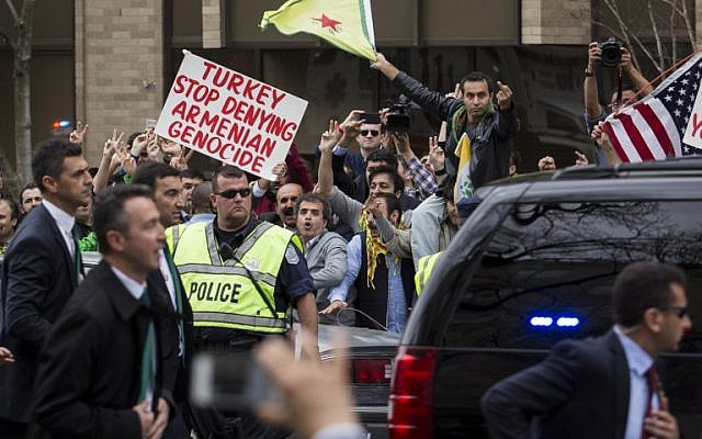 Protestors rallying against Turkish President Recep Tayyip Erdogan gesture toward his motorcade as it exits outside of the Brookings Institution, March 31, 2016 in Washington, DC. (Drew Angerer/Getty Images/AFP)