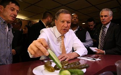 Republican presidential candidate John Kasich eats pickles while having lunch at PJ Bernstein's Deli Restaurant on April 16, 2016 in New York City.(Justin Sullivan/Getty Images/AFP)