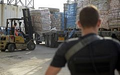 Illustrative. Defense Ministry contractors monitor the transfer of supplies and goods into the Gaza Strip through the Kerem Shalom Crossing on July 19, 2014. (Israel Defense Forces)