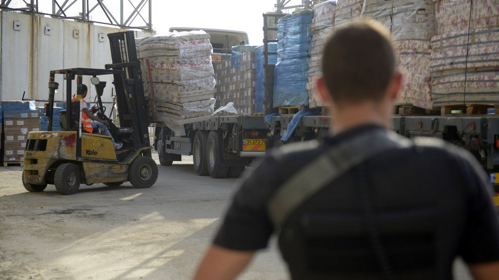 Illustration. Defense Ministry contractors monitor the transfer of supplies and goods into the Gaza Strip through the Kerem Shalom Crossing on July 19, 2014. (IDF Spokesperson's Unit)