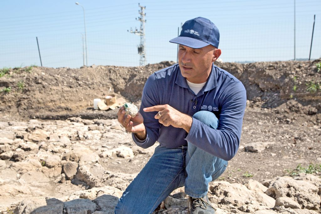 Excavation director Abdel Salam Sa'id examining one of the glass chunks found at a Roman-era site in northern Israel in 2015. (Shmuel Magal, courtesy of Israel Antiquities Authority)