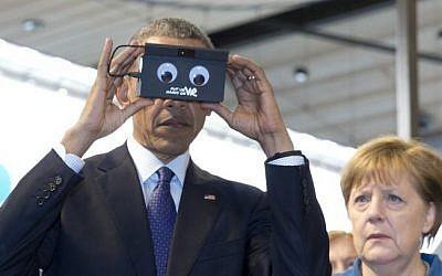 German Chancellor Angela Merkel looks on as US President Barack Obama tests VR goggles when touring the Hannover Messe, the world's largest industrial technology trade fair, in Hannover, northern Germany, Monday, April 25, 2016. (AP/Carolyn Kaster)