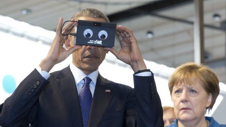 7c7ab41b8ff9 German Chancellor Angela Merkel looks on as US President Barack Obama tests  VR goggles when touring
